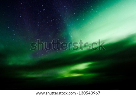 Northern lights above forest and mountain. Captured near Skibon, Norway - stock photo