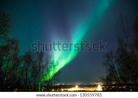 Northern lights and Big Dipper shine brightly over a city - stock photo
