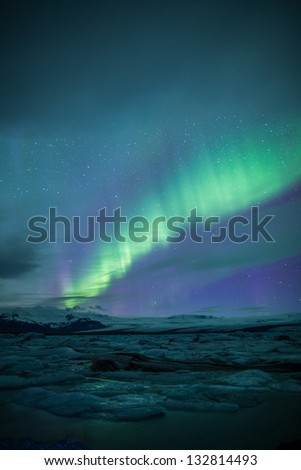 Northern lights (Aurora Borealis) above a lagoon in Iceland - stock photo