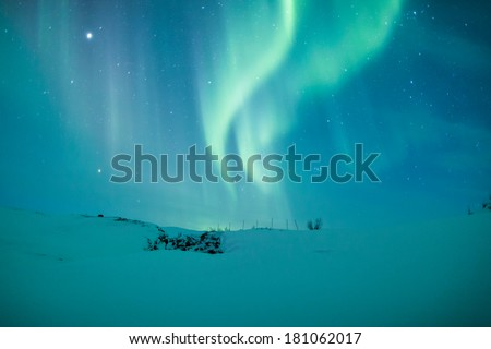 Northern lights (Aurora borealis) above a snowy mountain in Sweden - stock photo