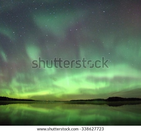 Northern lights (Aurora Borealis) in the night sky over a beautiful lake in Finland. Vibrant green colors on the sky and reflections on the still water of the lake. - stock photo