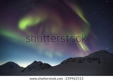 Northern Lights in the Arctic mountain landscape - stock photo