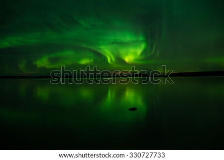 Northern lights over calm lake (Aurora borealis) in Sweden - stock photo