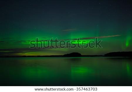 Northern lights over calm lake in Sweden (Aurora borealis) - stock photo