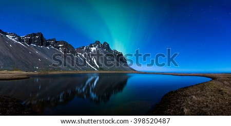 Northern lights reflected across a lake on the coast panoramic - stock photo