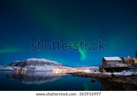Northern lights with reflections in the fjord, Norway, Tromso - stock photo