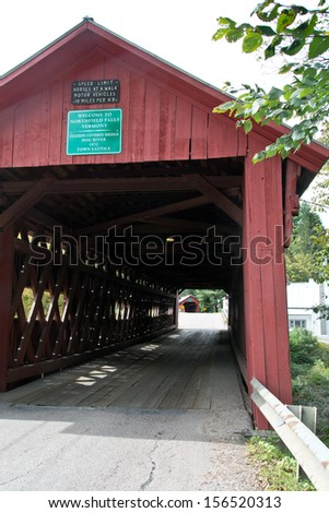 Northfield Falls, Vermont is traversed by a series of 2 covered bridges, Station bridge over the Dog River, and Lower bridge over Cox Brook. - stock photo