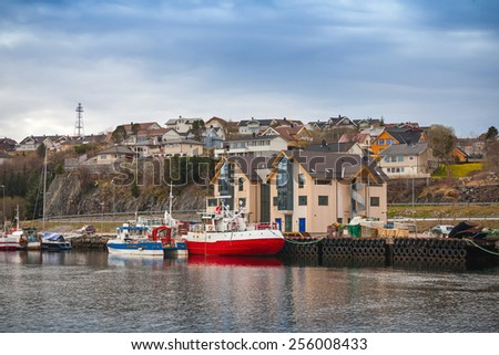 Norwegian fishing village with wooden houses and small moored boats - stock photo