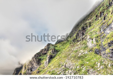 Norwegian fjord and mountains in cloudy weather - stock photo