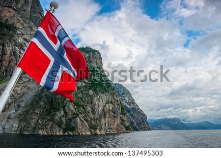Norwegian flag against fjord mountains - stock photo