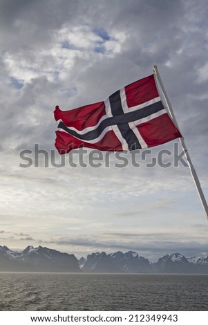 Norwegian flag and view to the Lofoten islands - stock photo