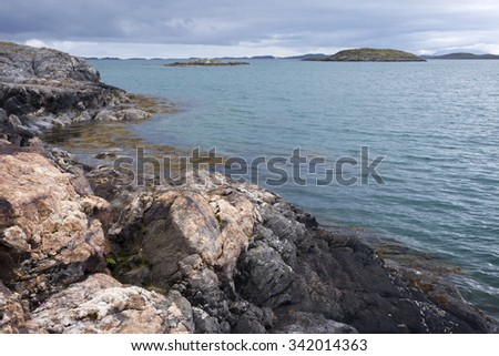 Norwegian landscape: view at sea from rocky island at half-cloudy day at Helgeland archipelago.   - stock photo