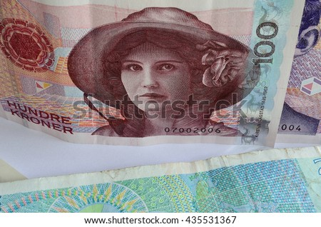 norwegian one hundred crown bank note on top of a two hundred crown note with a one thousand crown note in the background - stock photo