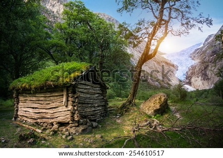Norwegian typical grass roof wooden old house and Briksdal glacier panorama, as  in a Magical forest  - stock photo