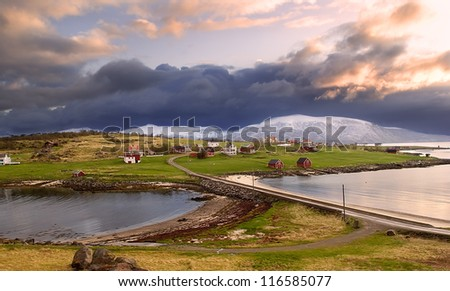 Norwegian village in the mountains with a gloomy sky - stock photo