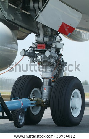 Nose wheel (front landing gear) of very large, wide-body airplane being towed at an airport. - stock photo