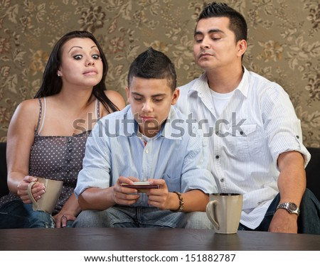 Nosey parents behind teenage son sending text messages - stock photo