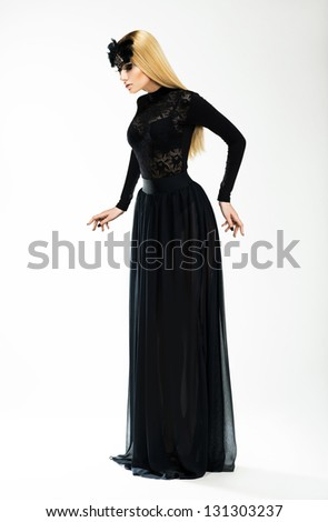Nostalgia. Expression. Beautiful Blond In Long Retro Dress and Black Mask - stock photo