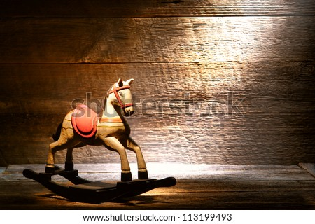 Nostalgic Americana scene of an antique reproduction wood toy rocking horse on aged wooden plank floor in a dusty old house attic lit by soft diffused sunlight through a window - stock photo