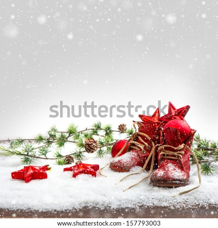nostalgic christmas decoration with antique baby shoes. festive background. retro style picture with snow effect - stock photo