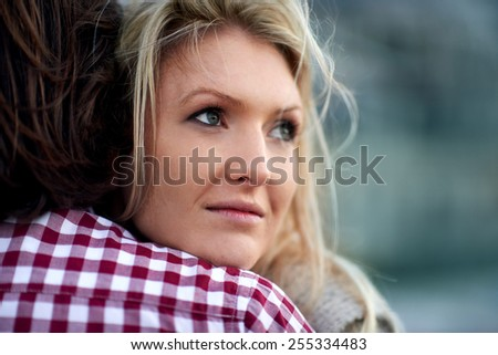 Nostalgic woman hugging her husband in the windy outdoors - stock photo