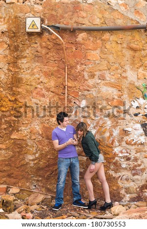Nosy and jealous girlfriend trying to  snoop into her boyfriends smartphone - stock photo