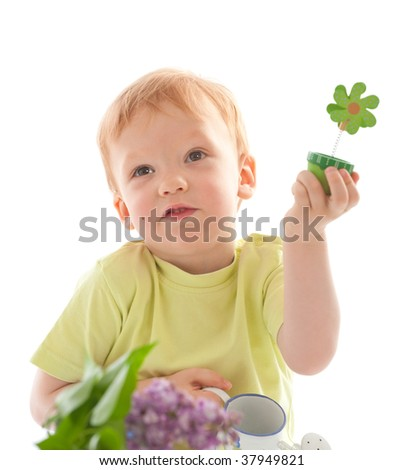 Not a real flower! Portrait of adorable happy boy using watering-pot water lilac flower - stock photo