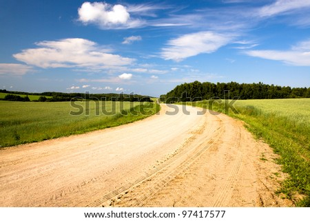 not asphalted rural rural road to summertime of year. Belarus - stock photo