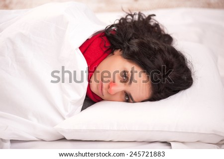 Not feeling too great. Closeup image of young sick woman lying in bed with red nose in thick scarf and looking at camera in frustration at copy space - stock photo