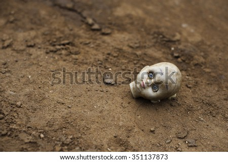 Not just a toy. The head of a broken toy is lying in the ground, blue eyes wide opened.  - stock photo