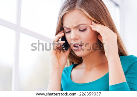 Not ready for this talk. Beautiful young women talking on the mobile phone touching her face and keeping eyes closed  - stock photo
