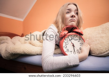 Not want to wake up concept. Funny young woman in bed waking up late. Unhappy sleepy girl holds red alarm clock. - stock photo