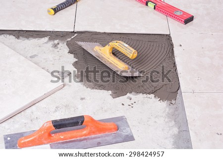 Notched trowel, spacers and prepared setting compound for tile - stock photo