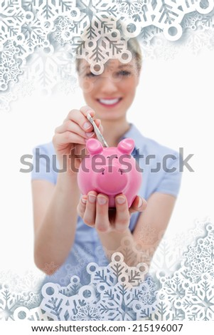 Note being put into piggy bank by woman against snowflakes on silver - stock photo