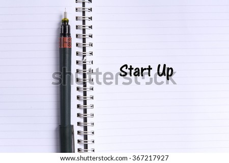 note book and a pen with START UP word. Selective focus,shallow depth of field. - stock photo