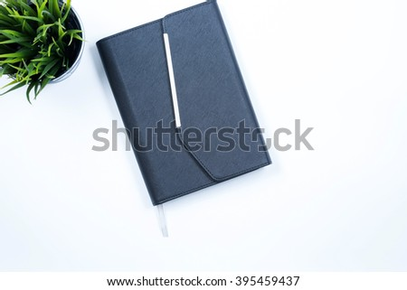 Note Book and grass in the bucket arrange in flatlay with white background. Selective focus with shallow depth of field. - stock photo