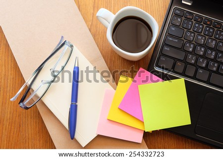 note book and laptop on wooden table with coffee  - stock photo