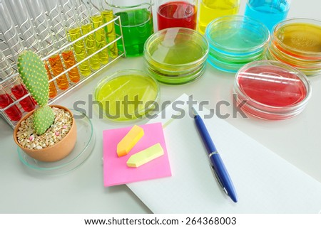 note book on laboratory table with Colorful fluid in  glass ware - stock photo