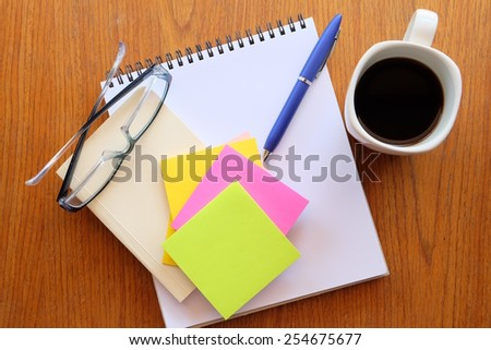 note book on the wooden table with black coffee  - stock photo