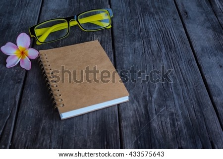 Note book on wooden background, flower, glasses. - stock photo