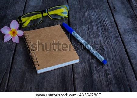 Note book on wooden background, pen, glasses, flower - stock photo