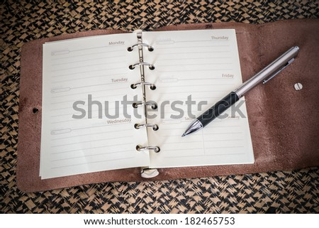 note book paper with pen on mat background - stock photo