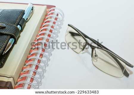 Note book pen and glasses stationery business training - stock photo