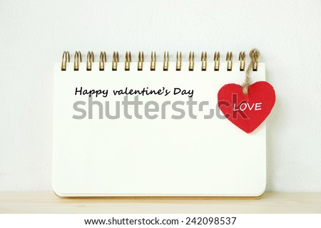 Note book with happy valentine's day words and red heart on table, valentine's day concept background - stock photo