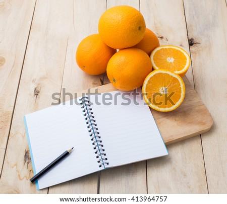 note book with orange on wooden floor - stock photo