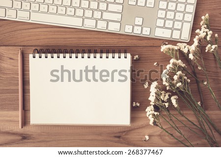 Note book with pencil on a wooden desk. Vintage tone - stock photo