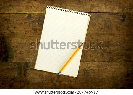 Note pad or memo pad on an old grungy wooden board or surface. For inserting your custom message or text.  - stock photo