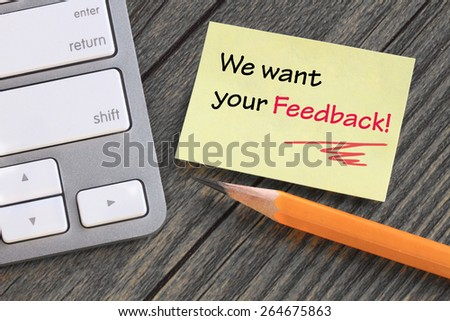 note showing we want your feedback, with desk background - stock photo