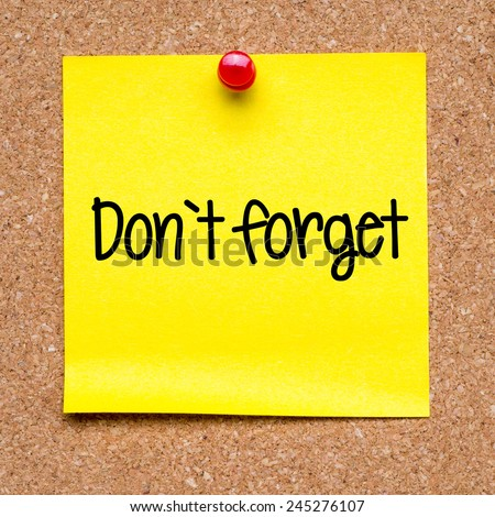 Note with don't forget. Blank yellow sticky note with don't forget pined on a cork bulletin board. - stock photo