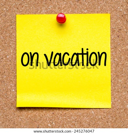 Note with on vacation. Blank yellow sticky note with on vacation pined on a cork bulletin board. - stock photo